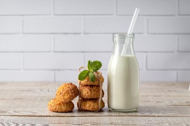 Bolinhos de coco saborosos e garrafa de leite na mesa de madeira branca