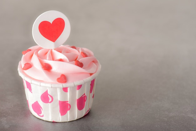 Bolinhos de creme de manteiga pastel rosa saboroso sobre fundo vermelho