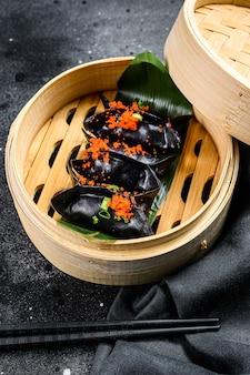 Bolinhos de dim sum pretos em cozinha asiática a vapor de bambu