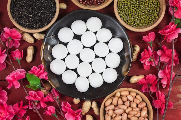 Bolinhos de doce em tigela na mesa, ang pow ou pacote vermelho e lingotes de ouro