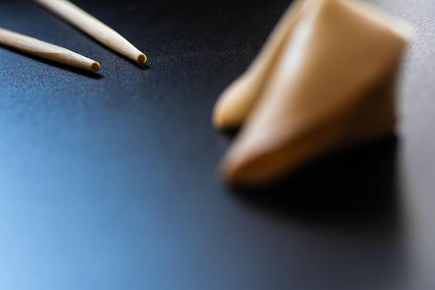 Bolinhos de fortuna no preto com chopsticks e espaço da cópia.