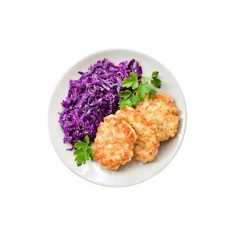 Bolinhos de frango e couve roxa cozida com sementes de cominho isoladas no fundo branco com traçado de recorte