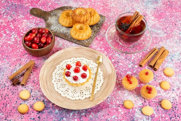 Bolinhos de frente com creme fresco e frutas frescas junto com canela e chá na superfície brilhante.