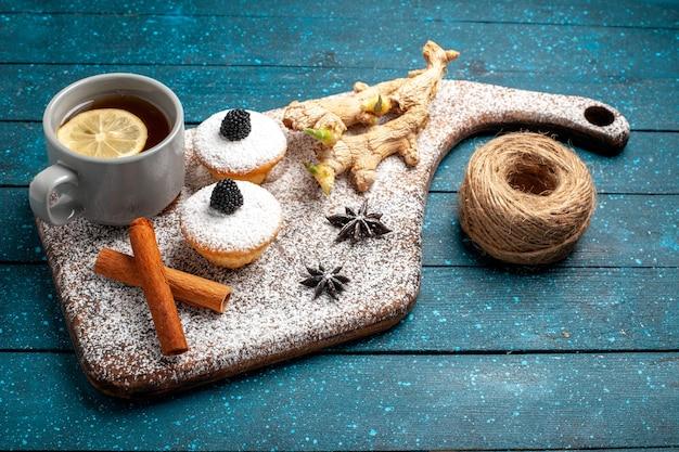 Bolinhos de frente com uma xícara de chá na mesa azul