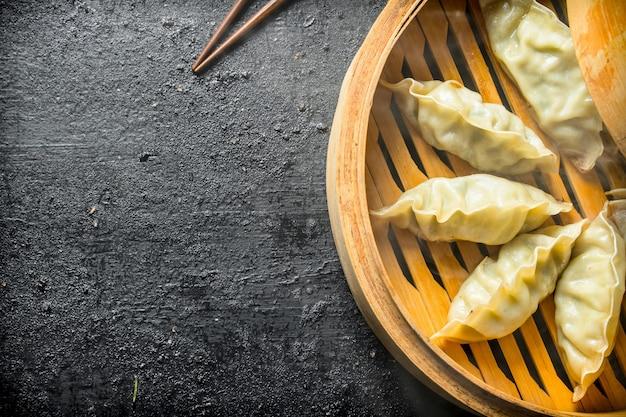 Bolinhos de gedza chineses perfumados em um vaporizador de bambu em uma mesa rústica preta
