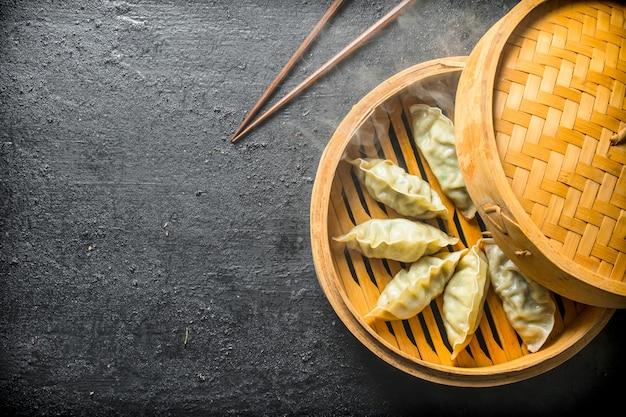 Bolinhos de gedza em um vaporizador de bambu em mesa rústica preta