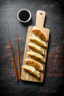 Bolinhos de gedza tradicionais chineses na tábua de madeira na mesa rústica escura.