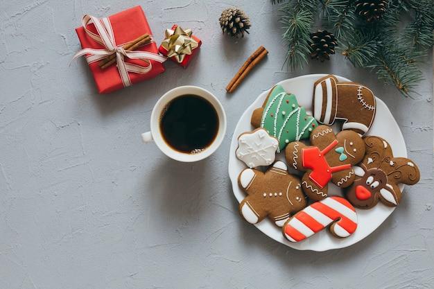 Bolinhos de gengibre de natal e uma xícara de café em um fundo cinza.
