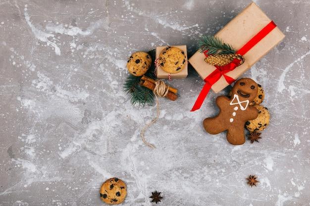 Bolinhos de gengibre e biscoitos de natal encontram-se diante de uma caixa presente
