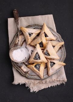 Bolinhos de hamantaschen com semente de papoula e risins e açúcar de confeiteiro em um prato, cozido para o festival judaico de purim.