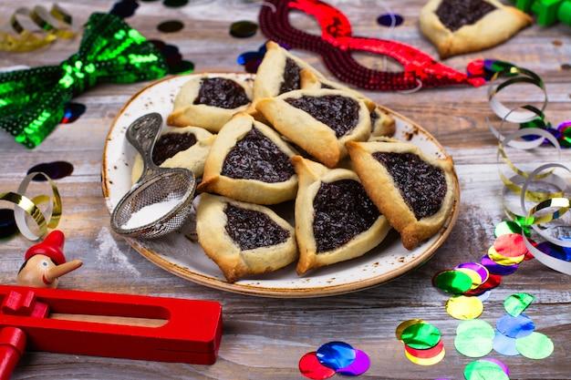 Bolinhos de hamantaschen judaicos tradicionais com doce da baga. conceito de celebração de purim