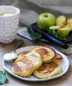 Bolinhos de maçã caseiros com creme de leite, café e maçãs verdes em uma madeira