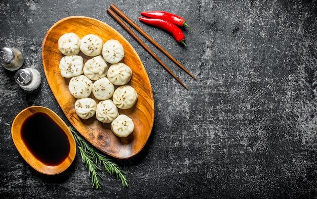 Bolinhos de manta com molho de soja, alecrim e pimenta na mesa rústica escura.