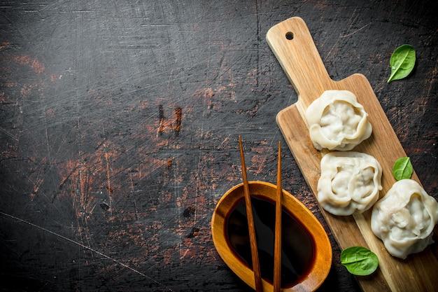 Bolinhos de manta em uma tábua de corte com molho de soja na mesa rústica escura