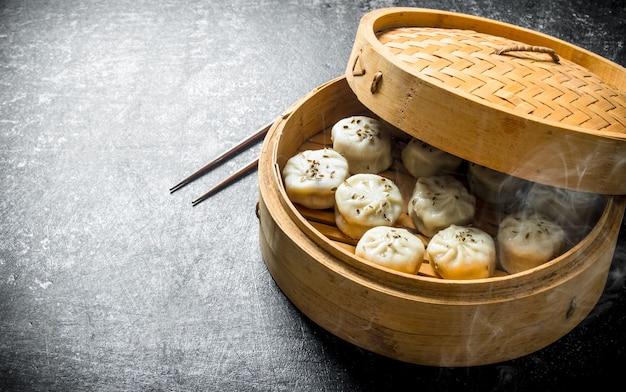 Bolinhos de manta recém cozidos em um vaporizador de bambu em uma mesa rústica escura
