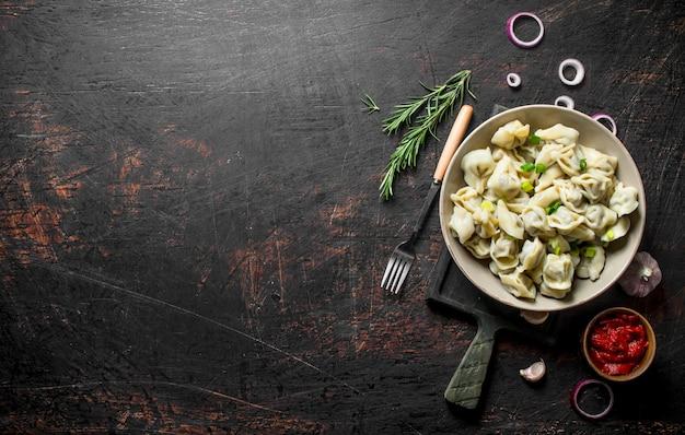 Bolinhos de massa com alho, rodelas de cebola e extrato de tomate na mesa rústica escura
