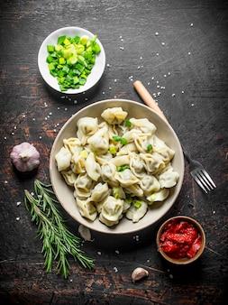 Bolinhos de massa com carne, cebola picada, extrato de tomate e alecrim em mesa rústica escura