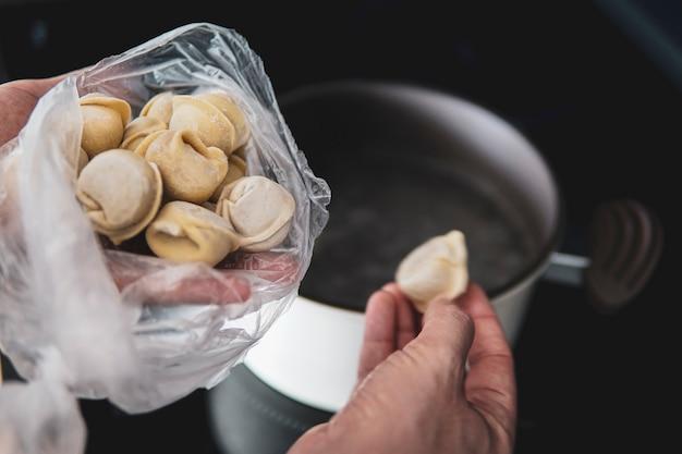 Bolinhos de massa com carne são fervidos em água fervente. foto de comida. o prato culinário bolinhos de massa ucranianos.