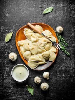 Bolinhos de massa com cogumelos e creme de leite na mesa rústica escura