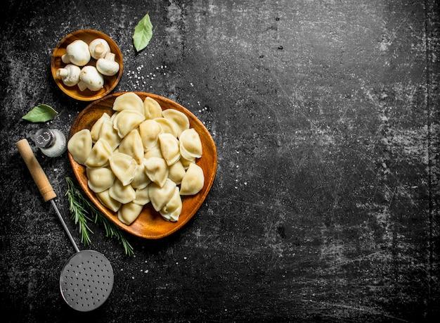 Bolinhos de massa com creme de leite, folha de louro e cogumelos. em fundo escuro rústico
