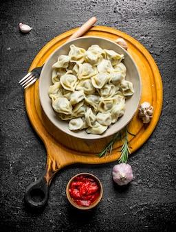 Bolinhos de massa com extrato de tomate, alho e alecrim na mesa rústica preta.