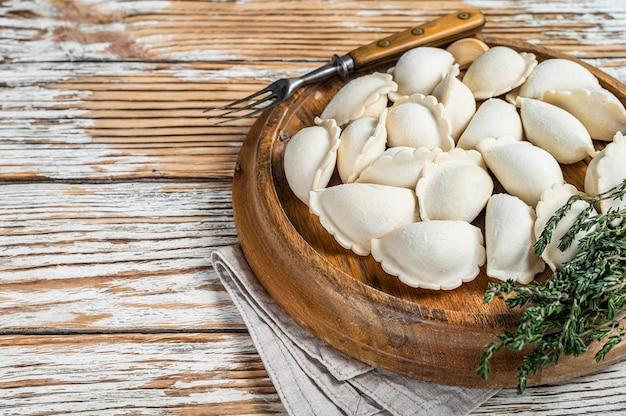 Bolinhos de massa congelados crus caseiros, vareniki, pierogi recheado com batata em uma placa de madeira. mesa de madeira branca. vista do topo.