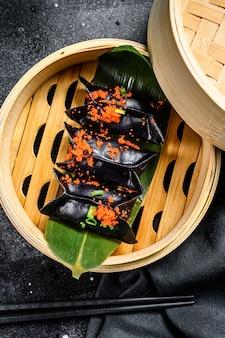 Bolinhos de massa cozinhados dim sum no navio de bambu. fundo preto. vista do topo