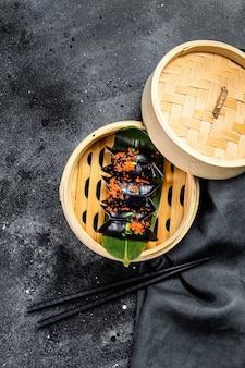 Bolinhos de massa cozinhados dim sum no navio de bambu. vista do topo