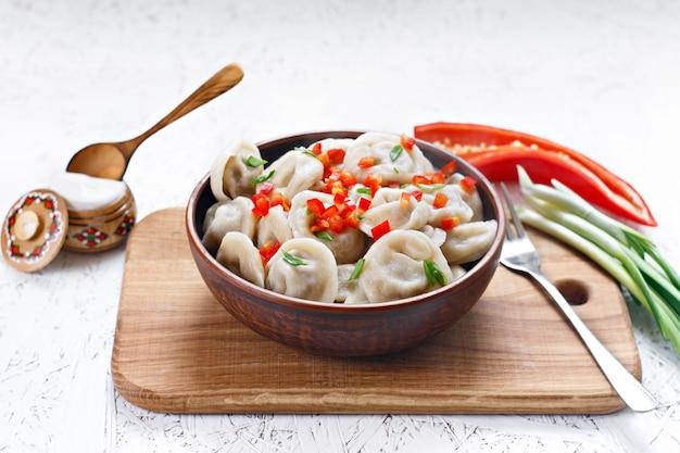 Bolinhos de massa cozinhados em um prato da argila com pimenta e cebolas.