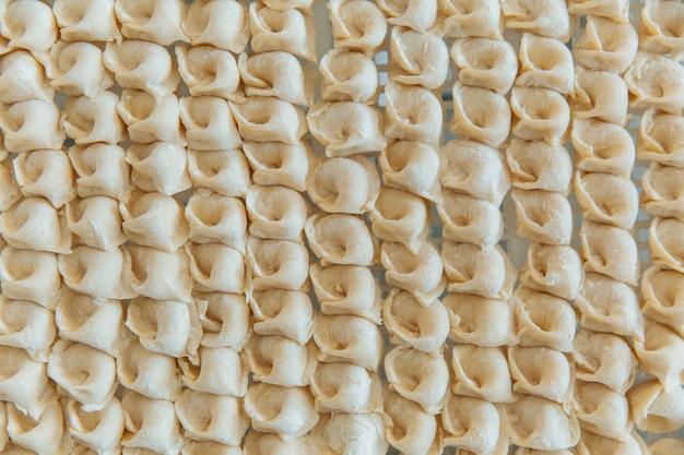 Bolinhos de massa crus em uma fileira. o conceito de cozinha, produtos semi-acabados