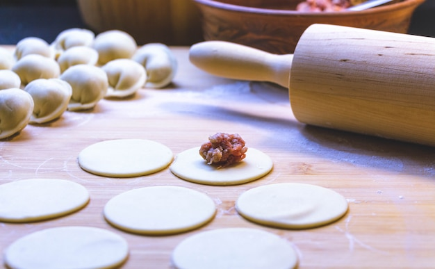 Bolinhos de massa crus - em uma placa de corte e ingredientes para bolinhos de massa caseiros em uma mesa de madeira.