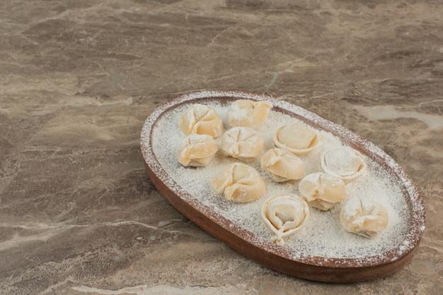 Bolinhos de massa crus na placa de madeira com farinha.