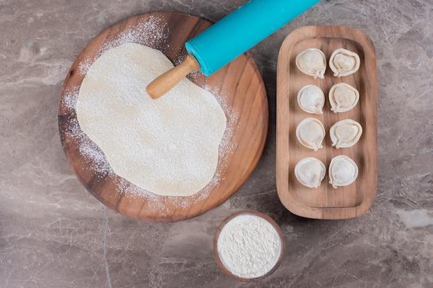 Bolinhos de massa crus na placa de madeira com massa e farinha em mármore.
