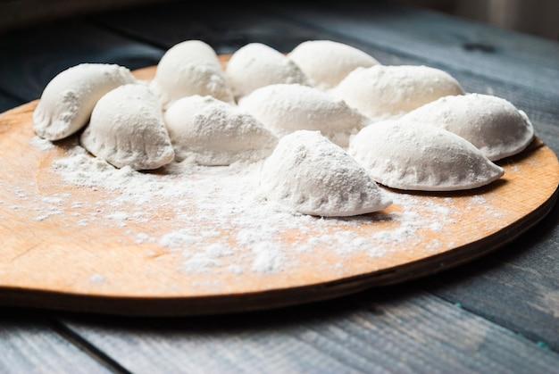 Bolinhos de massa crus polvilhados com farinha em uma placa de cozinha
