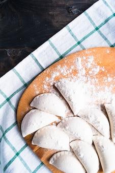 Bolinhos de massa crus polvilhados com farinha sobre uma tábua de cozinha e uma toalha listrada
