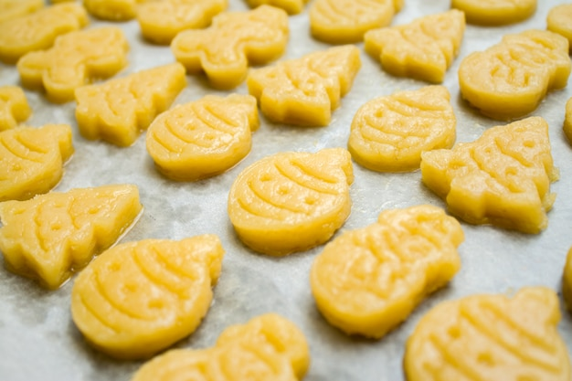 Bolinhos de massa de biscoito de massa crua de natal para a forma de childrenin de bola, abeto, boneco de neve