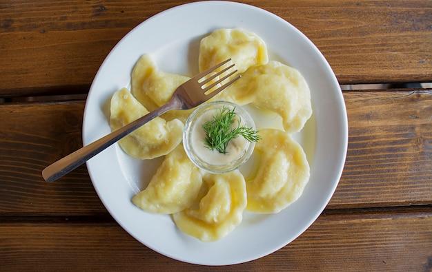 Bolinhos de massa em um prato branco com creme de leite. -
