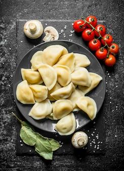 Bolinhos de massa em um prato e tomate cereja em uma mesa escura e rústica