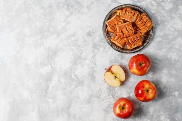 Bolinhos de massa folhada cheios de compota de maçã e maçãs vermelhas frescas em concreto claro