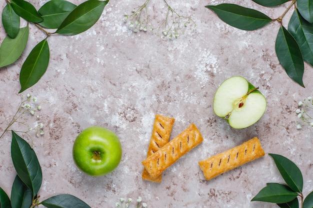 Bolinhos de massa folhada de maçã no prato de forma de maçã com maçãs frescas, vista superior
