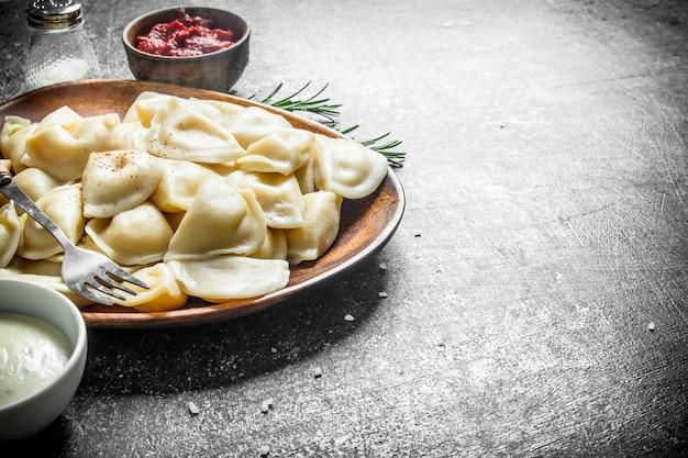 Bolinhos de massa num prato com pasta de tomate em uma tigela na mesa rústica escura.