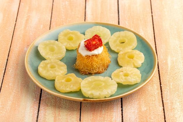 Bolinhos de massa oriental dentro do prato com anéis de abacaxi seco com creme branco na mesa de madeira