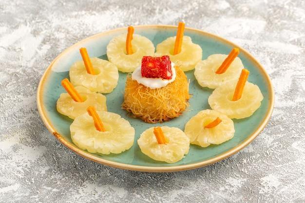 Bolinhos de massa oriental dentro do prato com anéis de abacaxi seco com creme branco