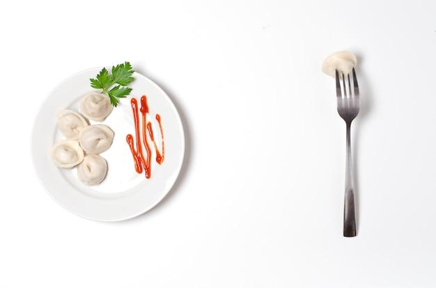 Bolinhos de massa tradicionais do russo, ravioli, bolinhos de massa em uma placa branca com molho e salsa vermelhos.