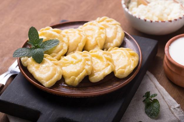 Bolinhos de massa ucranianos, pierogi ou pyrohy, varenyky, vareniki, servidos com queijo cottage a bordo. cozinha nacional russa, produto de padaria caseiro orgânico natural, vista de cima.