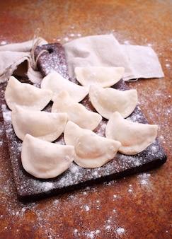 Bolinhos de massa (varenili) com batata polvilhada com farinha em uma placa de madeira velha