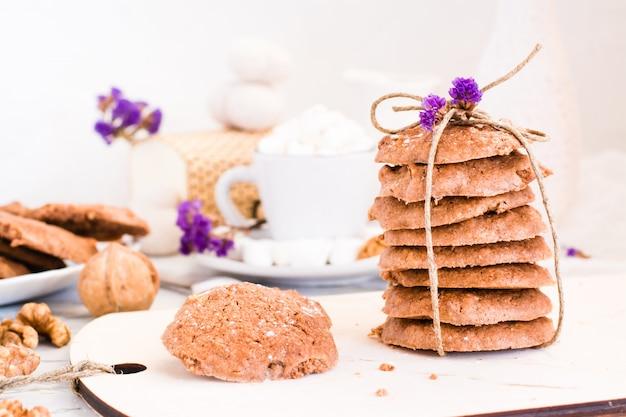 Bolinhos de microplaqueta de chocolate caseiros com as nozes na placa da cozinha. cenário de mesa para café da manhã