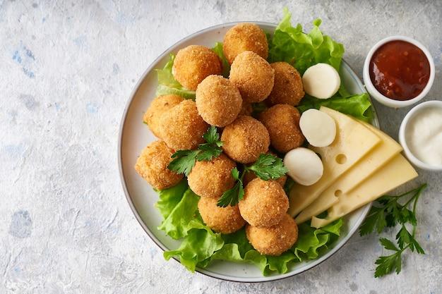 Bolinhos de queijo, aperitivo com ervas e molhos em um prato sobre uma mesa cinza