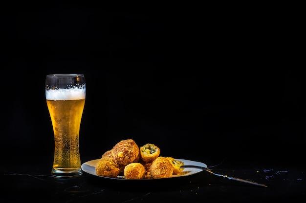 Bolinhos de queijo com alho e endro no interior para um lanche com um copo de cerveja