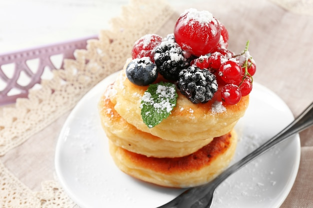 Bolinhos de queijo cottage com frutas no prato, closeup